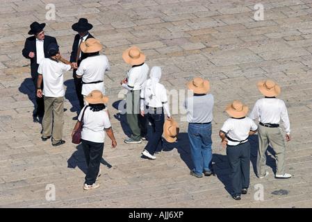Israel jerusalem Old City Jewish quarters group of tourists talking to local ultra orthodox Jews - Stock Photo