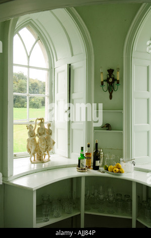 Recessed gothic window with shutters and glassware shelf with drinks bottles - Stock Photo