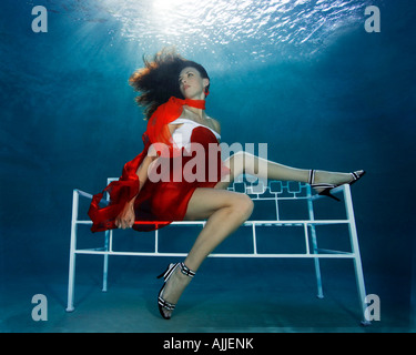 Woman underwater in pool wearing fashion outfit - Stock Photo