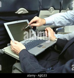 Business people using laptop on an aeroplane - Stock Photo
