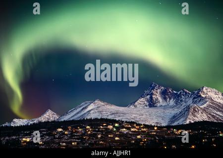Aurora Borealis over hillside neighborhood Chugach Mountains Anchorage Alaska SC Composite Winter - Stock Photo