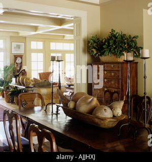 Open plan dining and living room with antique furniture and dried gourds table display - Stock Photo