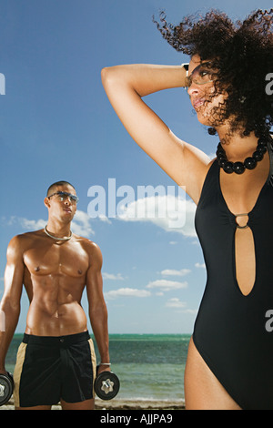 A young man and woman on the beach - Stock Photo