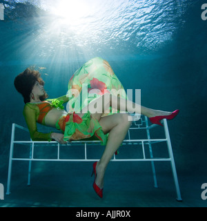 Woman in fashion outfit underwater in pool - Stock Photo
