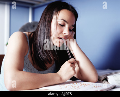Girl doing homework in bedroom - Stock Photo
