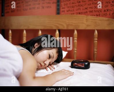 Teenage girl sleeping in bed - Stock Photo