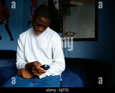 Boy text messaging in bedroom - Stock Photo