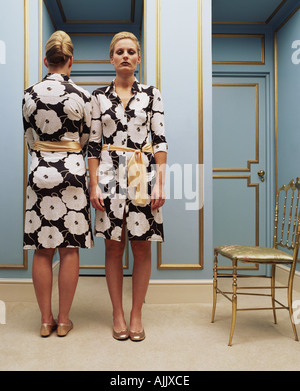 Two women wearing the same dress - Stock Photo