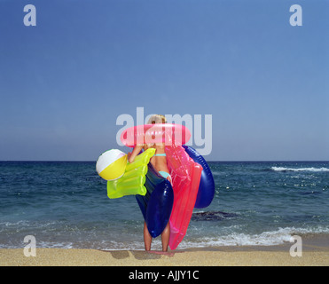 Woman carrying inflatable toys on beach - Stock Photo