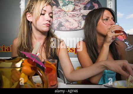 Two women with food and cocktails - Stock Photo