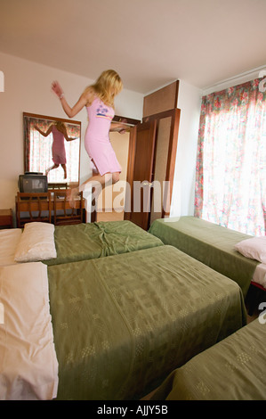 Woman jumping on hotel bed - Stock Photo