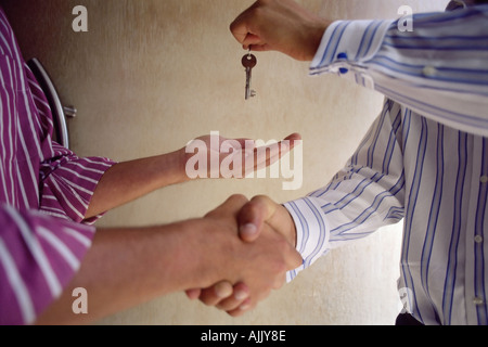 Handing over keys and shaking hands - Stock Photo