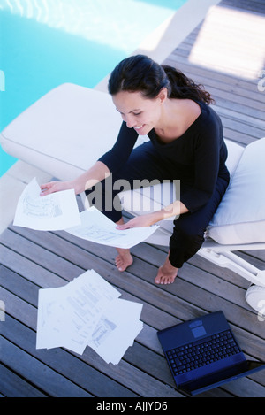 Woman working by the pool - Stock Photo