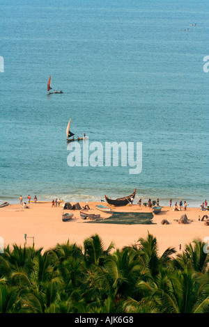 Lush greenery with the golden beach and the sailing boats on the background at Vizhinjam, Kerala, India - Stock Photo