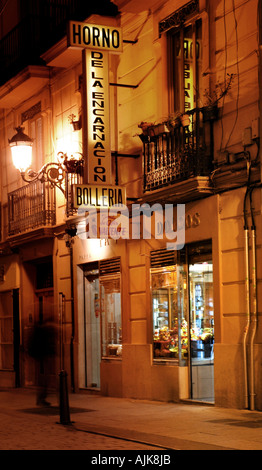 blurred figure of a man walking past a pastry shop open late in the evening in Valencia Spain - Stock Photo