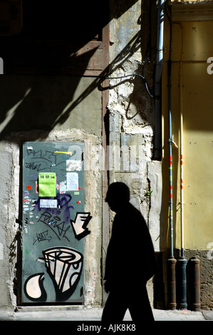 silhouette of old man against bright sunlight walking past metal door painted with graffiti in a side street Valencia - Stock Photo