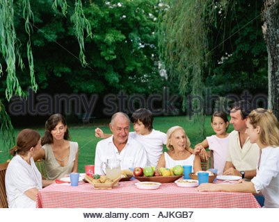 Family having a meal in the garden - Stock Photo