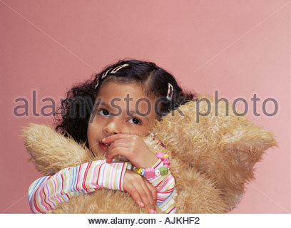 Girl hugging her teddy bear - Stock Photo