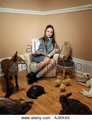 Girl reading story to stuffed animals - Stock Photo