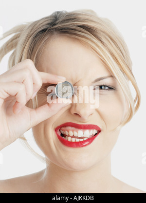 Woman holding Euro coin to her eye - Stock Photo