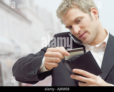 Man on mobile with credit card - Stock Photo