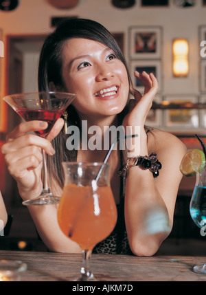 Young woman drinking a cocktail in a bar - Stock Photo