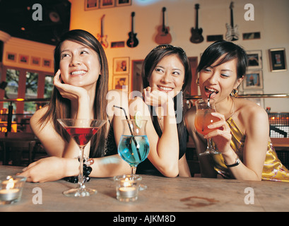 Three young women drinking cocktails in a bar - Stock Photo