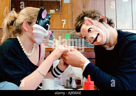Couple wearing face masks in cafe - Stock Photo