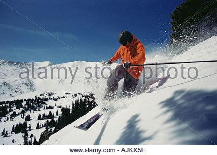 Man skiing down mountainside - Stock Photo