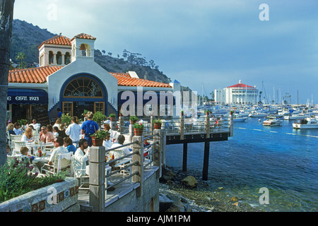 Tourists on restaurant balcony with Casino  and yachts at Avalon Bay on Catalina Island off Southern California - Stock Photo