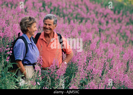 Senior couple hiking in field of purple flowers - Stock Photo