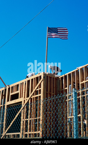 Two construction workers building new home with wood framing and US flag Santa Monica boulevard Los Angeles CA - Stock Photo
