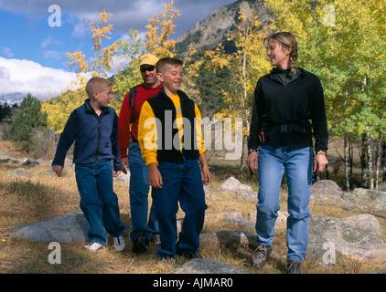A family of four hiking amid fall color in Rocky Mtns of CO - Stock Photo