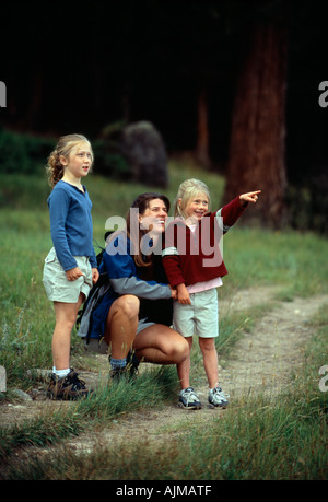 A mother and her daughters stop to talk along a trail in Rocky Mtn Nat l Park CO - Stock Photo