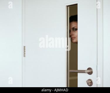 Woman peering through door - Stock Photo