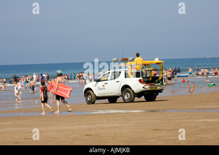 RNLI Beach Lifeguards Rescue vehicle on crowded beach in August Woolacombe Devon UK - Stock Photo