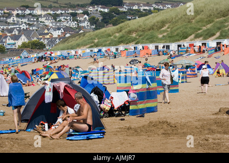 Holidaymakers with tents umbrellas and windbreaks on crowded sandy beach in August Woolacombe Devon UK - Stock Photo