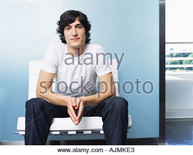 Young man sitting on chair - Stock Photo