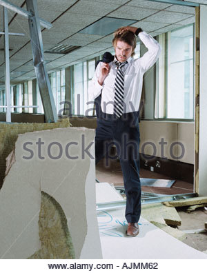 Businessman looking at vandalised office room - Stock Photo