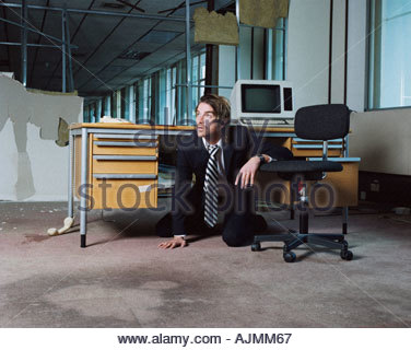 Businessman emerging from under desk - Stock Photo