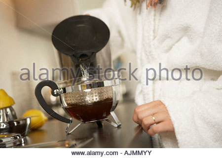 Mid section view of a woman pouring water into a container of herbal tea - Stock Photo