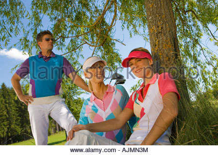 Two mid adult women sitting under a tree smiling with a mid adult man standing beside them - Stock Photo