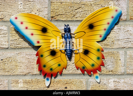 Metal garden ornament butterfly on a house wall - Stock Photo