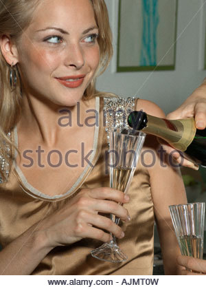 Close-up of a person's hand pouring champagne into a champagne flute held by a young woman - Stock Photo
