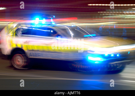 An emergency services vehicle speeding through a London street at night. - Stock Photo