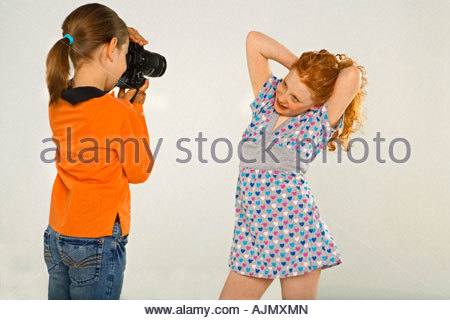 Side profile of a girl taking a picture of her friend - Stock Photo