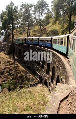 India Himachal Pradesh transport Shimla Kalka narrow gauge railway train passing over bridge - Stock Photo