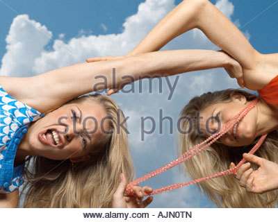 Low angle view of two young women fighting - Stock Photo