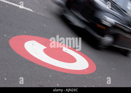 congestion charge sign signage in road with London taxi - Stock Photo