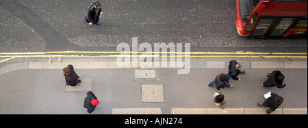 aerial view of commuters and office workers on pavement with bus passing on road - Stock Photo